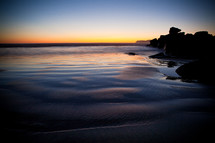 tide washing onto a shore at dusk