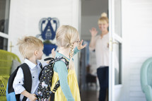 mother waving goodbye to her kids as the leave for school