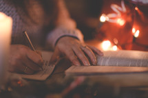 a woman reading a Bible and writing in a journal at Christmas