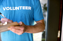 "A man writing with a pen on a clipboard while wearing a t-shirt saying, ""volunteer."""