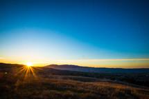 sunburst over a mountaintop landscape at sunset