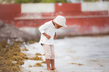 a boy dipping his toes in the sand