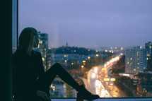 a woman sitting in a window sill looking out at a city at night