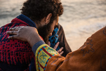 comforting a man on a beach