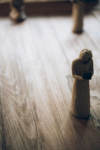 Figurines of wisemen bearing gifts on wooden floor.