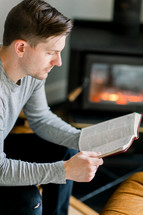 a man reading a Bible by a fireplace