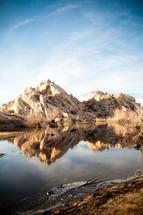 reflection of desert rocks in a pond