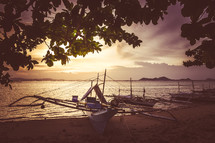 boats beached on a shore at sunrise