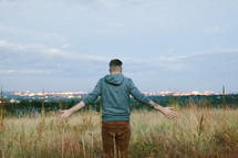 a man standing in a field of tall grasses praying over city