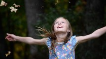 A little girl with arms outstretched watching in amazement autumn leaves fall