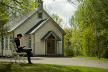 a man sitting on a bench in front of a chapel reading a Bible