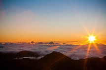 sunrise over mountaintops in the clouds
