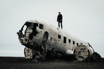 a man standing on a wreckage of an airplane crash site