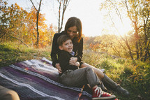 mother tickling her son as they sit on a blanket in the grass