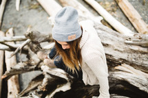 woman in a wool cap sitting on driftwood