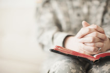Female soldier in uniform praying over an open Bible.