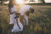 a family walking through tall grass at sunset