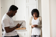 couple texting in a kitchen