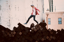 a boy walking over a pile of lumber