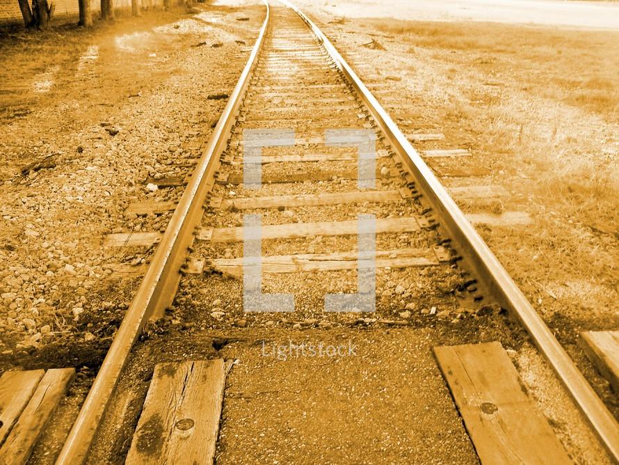 A historic photograph of a set of railroad tracks in a sepia tone color.