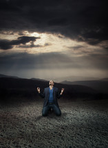 a man kneeling under radiating light