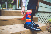 A man wearing Superman socks.