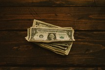Dollar bills stacked on a wooden table