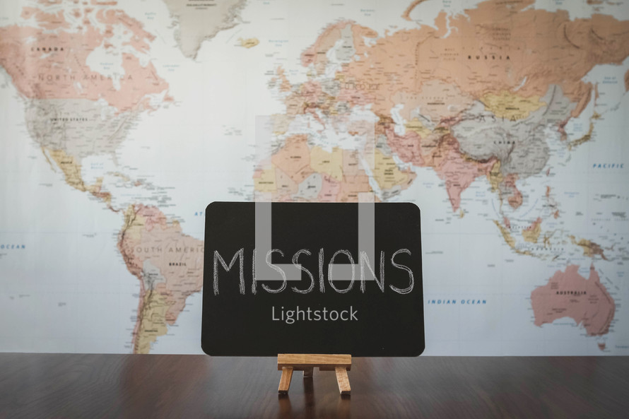 world map and word missions on a sign