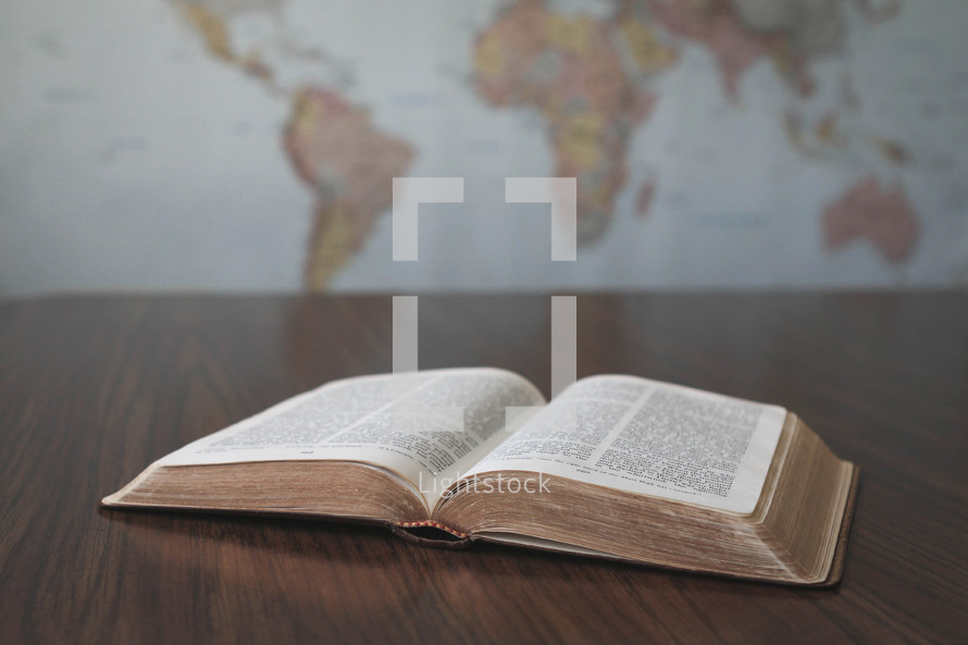 world map and open Bible on a desk