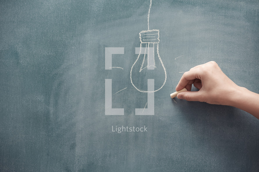 hand drawing a lightbulb on a chalkboard