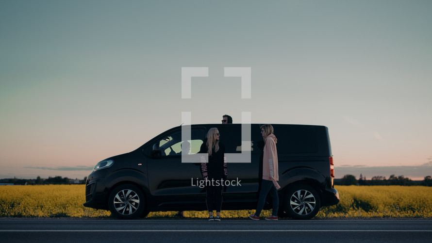 friends standing beside of their van parked on the side of the road