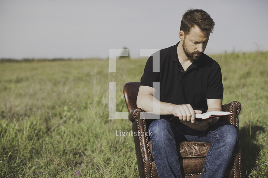 A man sitting in a leather chair reading a Bible outdoors