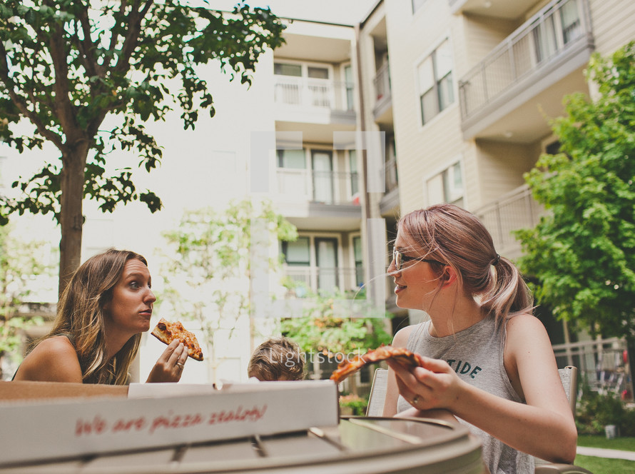 women eating pizza on a patio