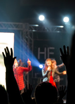 A worship team sings as people lift their hands