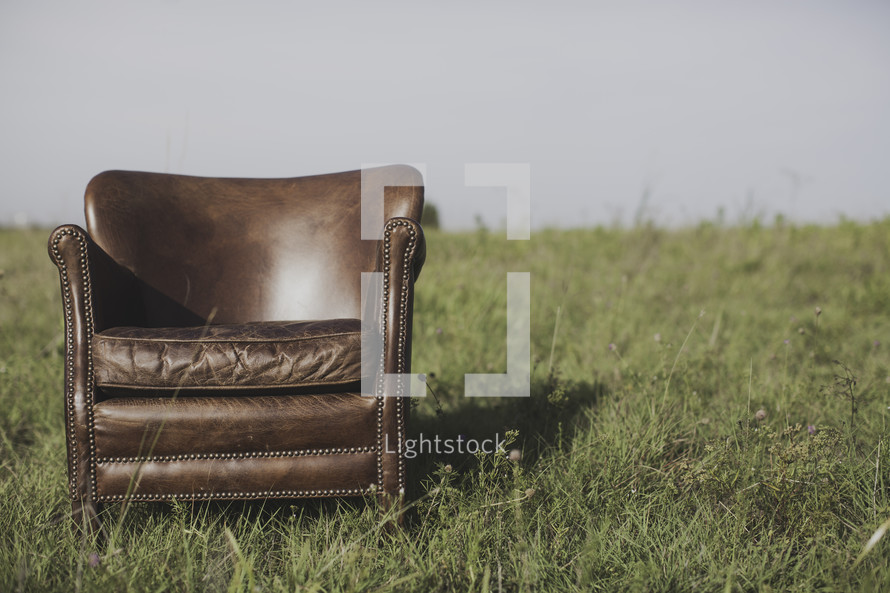 a leather chair alone in a field