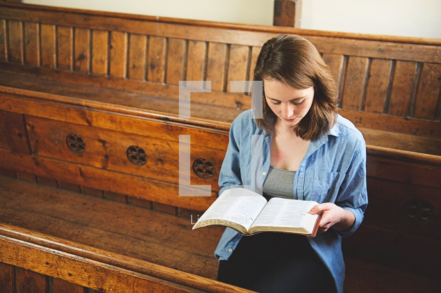a woman reading alone sitting in the pews of a church
