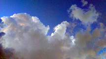 Blue Skies behind clouds with a silver lining of gray clouds parting after a storm.