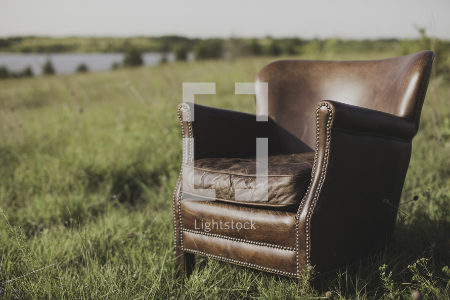 a leather chair in a field