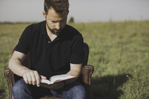 a man sitting in a chair outdoors reading a Bible