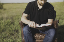 a man sitting in a leather chair reading a Bible in a field