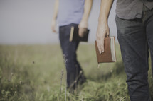 men standing in a field of tall grass holding Bibles