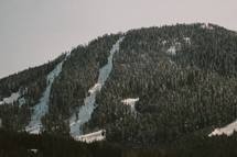 A mountain with snow covered ski slopes.