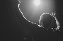 man with raised hands under a spotlight