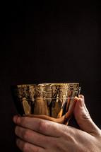 Hands holding a golden wine goblet.