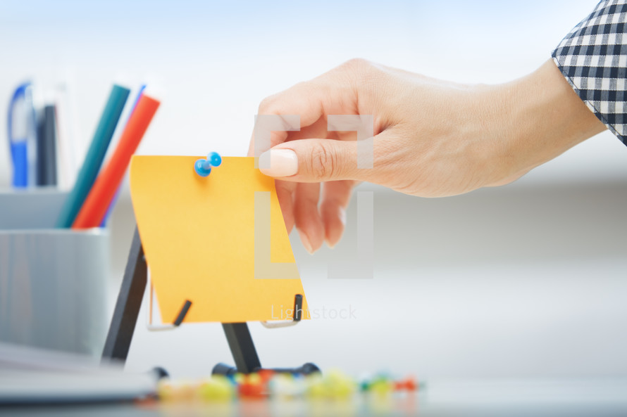 a woman reaching for a blank sticky note