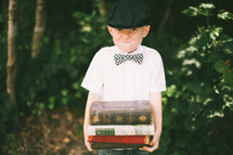 boy child straining holding a stack of books
