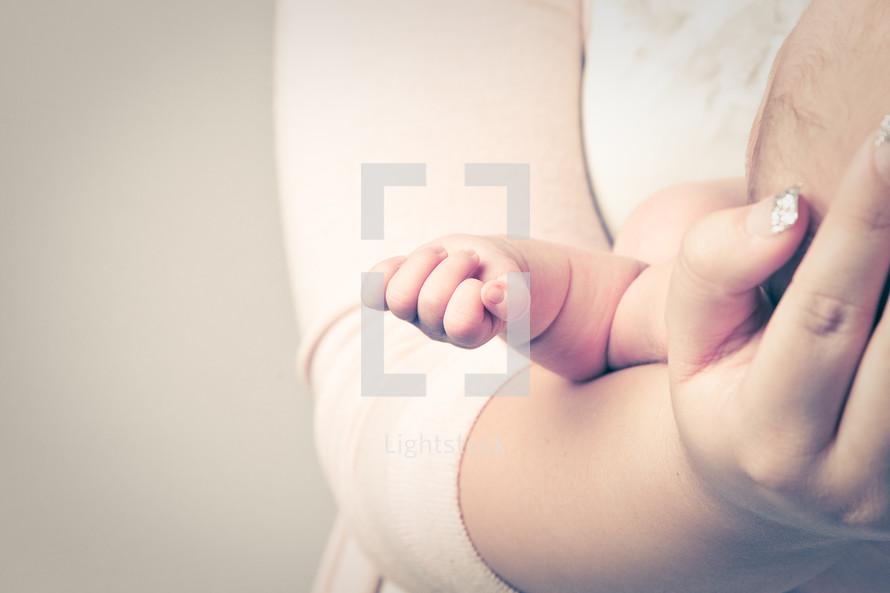mother's hands cradling a newborn