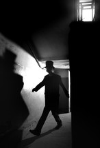 a man in a top hat walking in the shadows