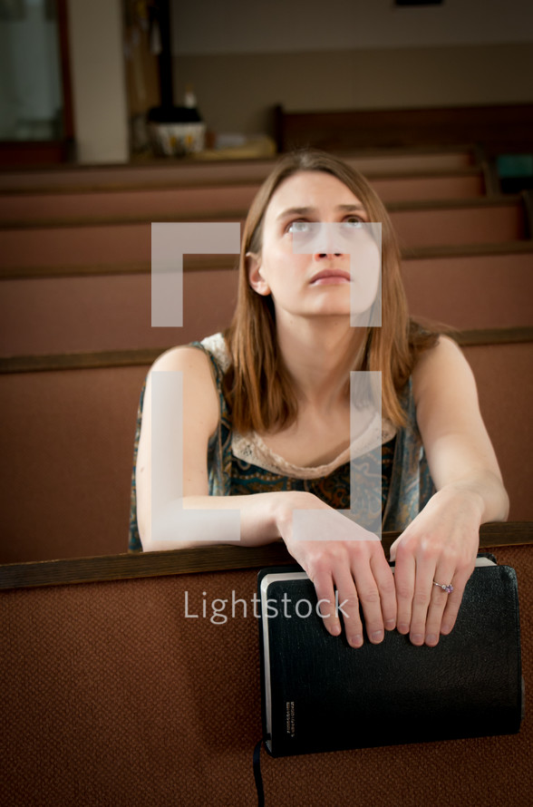 A woman holding a Bible sitting in a church pew looking to God