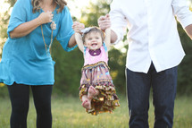 a mother and father swinging their toddler daughter